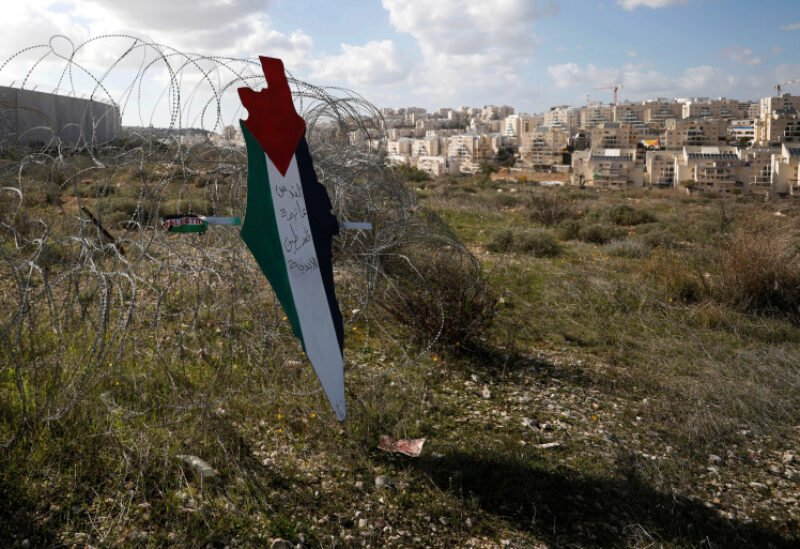 Representation of a map with the colors of the Palestinian flag is placed on a fence as a Jewish settlement is seen during a protest against Trump's Middle East peace plan, in the village of Bilin in the Israeli-occupied West Bank