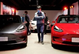 FILE PHOTO: A man wearing a face mask following the coronavirus disease (COVID-19) outbreak walks by Tesla Model 3 sedans and Tesla Model X sport utility vehicle at a new Tesla showroom in Shanghai, China May 8, 2020.