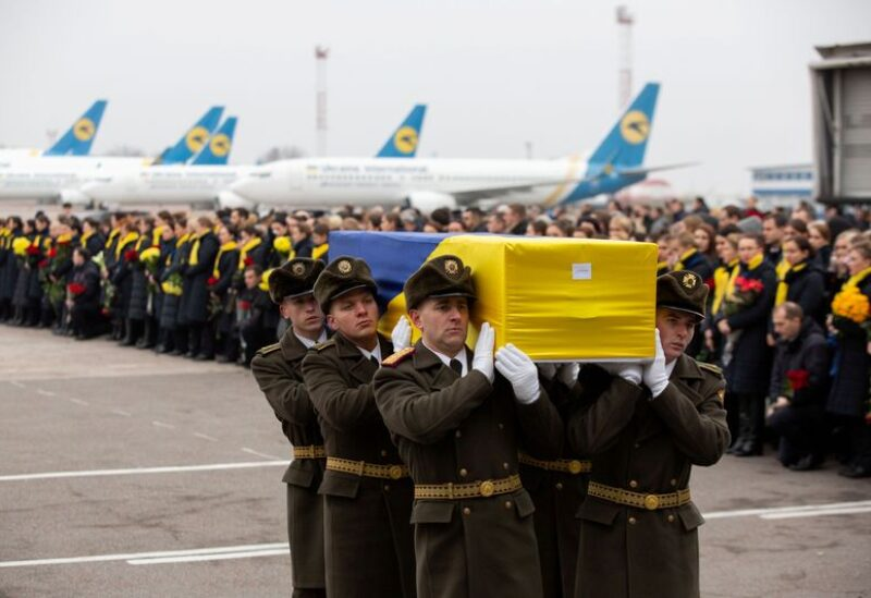 FILE PHOTO: Soldiers carry a coffin containing the remains of one of the eleven Ukrainian victims of the Ukraine International Airlines flight 752 plane disaster, at Boryspil International Airport, outside Kiev, Ukraine, January 19, 2020.