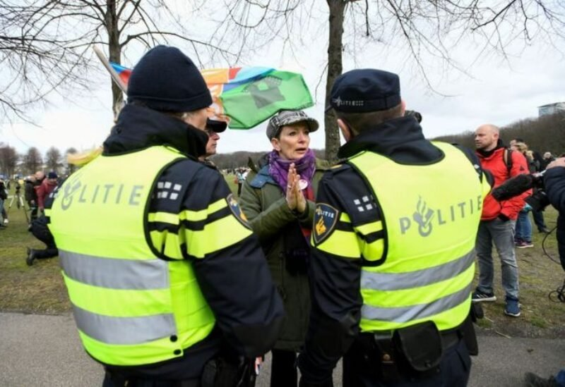 A woman speaks with police officers, as people protest against coronavirus disease (COVID-19) restrictions in The Hague, Netherlands, March 14, 2021.