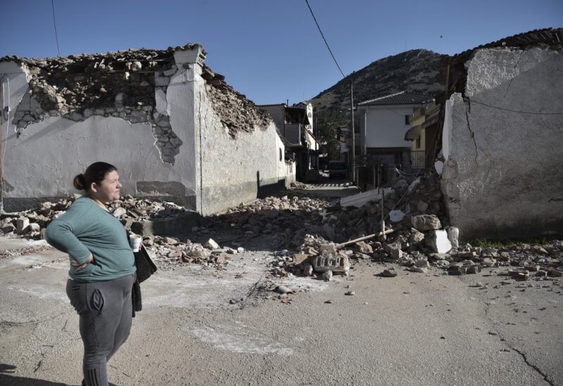FILE PHOTO: A woman stands by damaged old buildings in the village of Damasi, near the town of Tyrnavos, after a strong 6,3-magnitude earthquake hit the Greek central region of Thessaly on March 3.