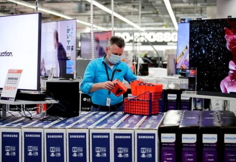 FILE PHOTO: An employee wearing a protective mask works at a Saturn electronic store as the coronavirus disease (COVID-19) lockdown measures are eased in Berlin, Germany, March 11, 2021.