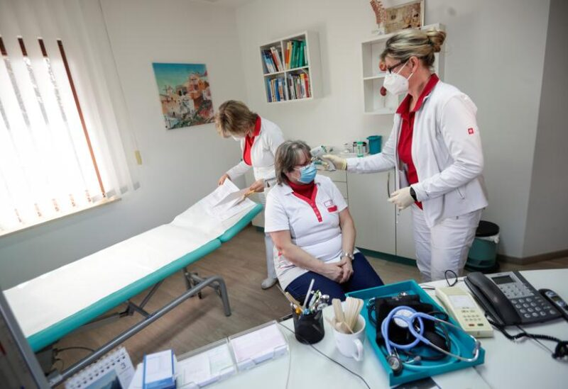 FILE PHOTO: A health worker checks the temperature of the nurse before vaccination, in the state of Brandenburg where the first coronavirus vaccinations are given in doctors' surgeries, in Senftenberg, Germany, March 3, 2021.