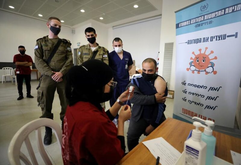 FILE PHOTO: A Palestinian laborer who works within Israel or its settlements in the occupied West Bank, is vaccinated at an Israeli facility at Shaar Efraim crossing from Israel to the West Bank, March 8, 2021.