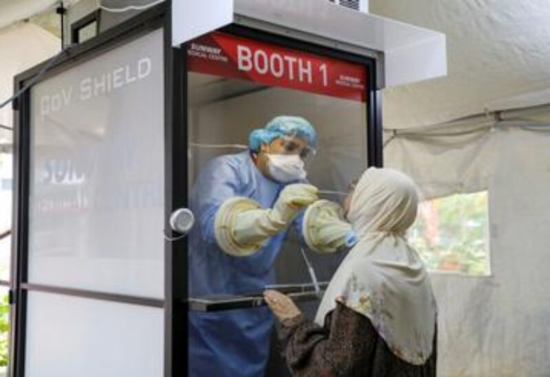 FILE PHOTO: A Medical worker collects a swab sample from a woman to be tested for the coronavirus disease (COVID-19) at Sunway Medical Centre, in Subang Jaya, Malaysia March 12, 2021.