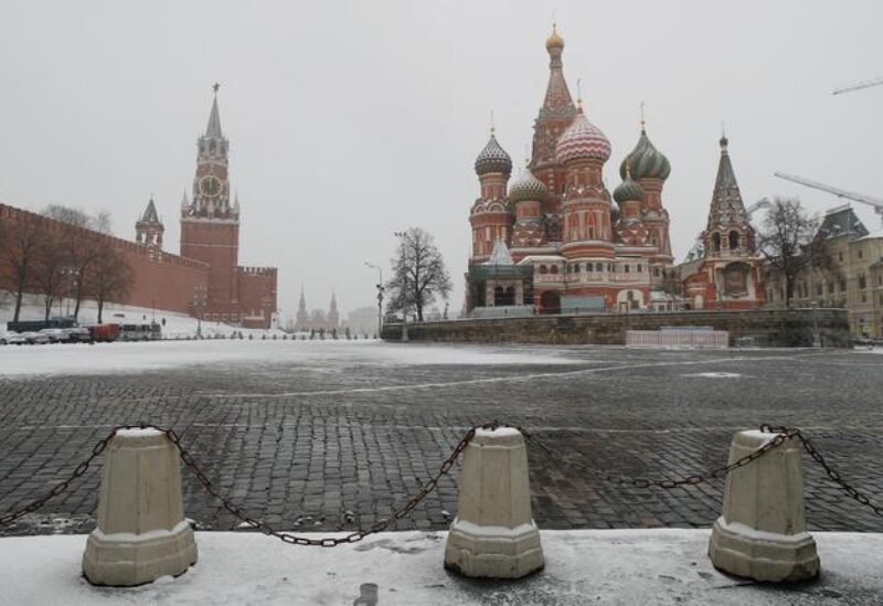 FILE PHOTO: The clock on Spasskaya tower showing the time at noon, is pictured next to Moscow's Kremlin, and St. Basil's Cathedral as they stand on an empty square, during the coronavirus disease (COVID-19) outbreak, in Moscow, Russia, March 31, 2020.