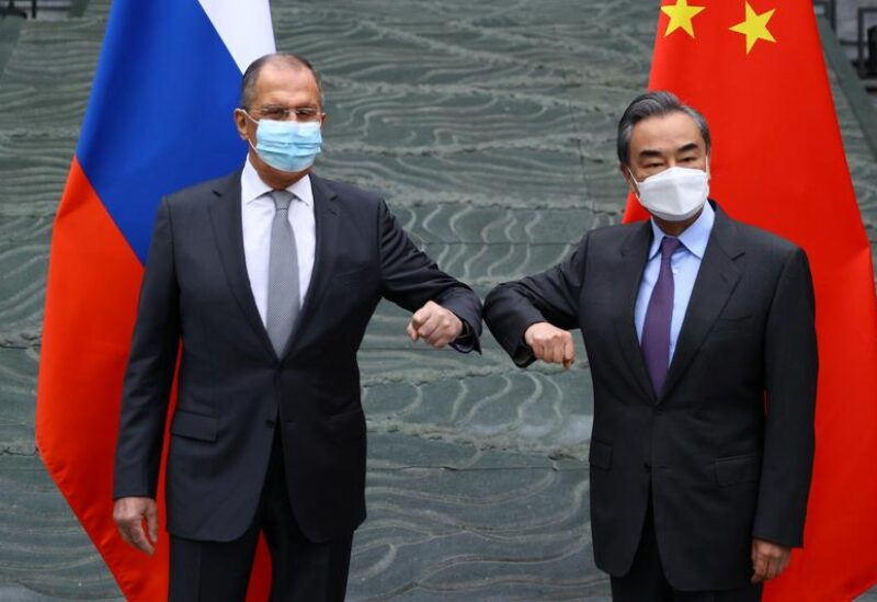 Russia's Foreign Minister Sergei Lavrov and China's State Councilor and Foreign Minister Wang Yi wearing protective face masks pose for a picture during a meeting in Guilin, China March 22, 2021.