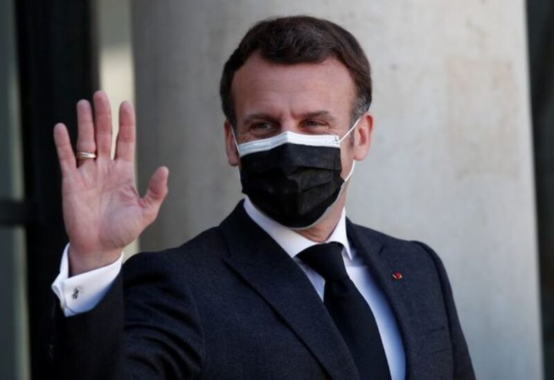 FILE PHOTO: French President Emmanuel Macron, wearing a protective face mask, waves to journalists as he welcomes President of the Kurdistan region in Iraq Nechirvan Barzani (not seen) before a meeting at the Elysee Palace in Paris, France, March 30, 2021.