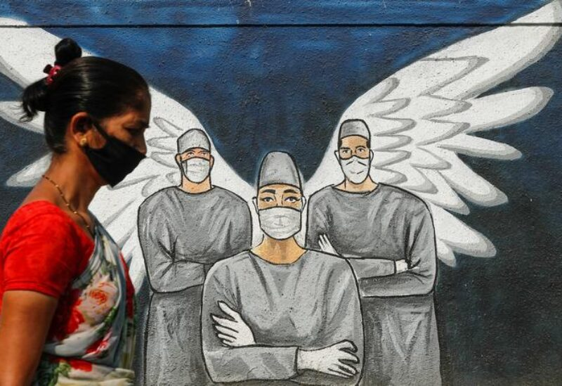 A woman wearing a protective mask walks past a graffiti amidst the spread of the coronavirus disease, on a street in Navi Mumbai, India, March 8, 2021.