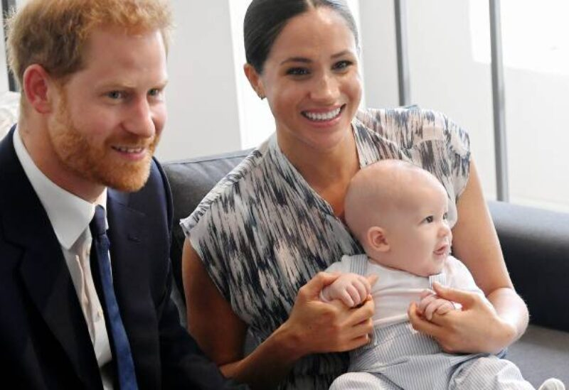 Prince Harry and his wife, Meghan Markle, holding their baby.
