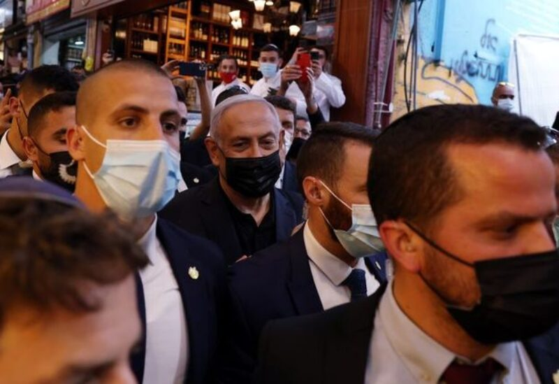 Israeli Prime Minister Benjamin Netanyahu surrounded by bodyguards as he visits Mahane Yehuda market, a day before the March 23 general election, in Jerusalem March 22, 2021.