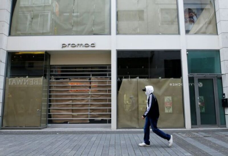 FILE PHOTO: A man walks along a closed shop at the main shopping street Hohe Strasse amid the coronavirus disease (COVID-19) pandemic in Cologne, Germany, March 18, 2021.