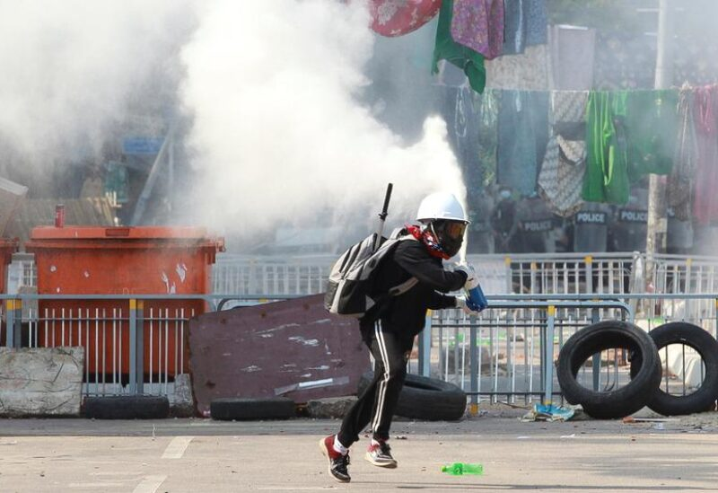 FILE PHOTO: An anti-coup demonstrator sprays a fire extinguisher as he runs away from a barricade during a protests in Yangon, Myanmar, March 9, 2021.
