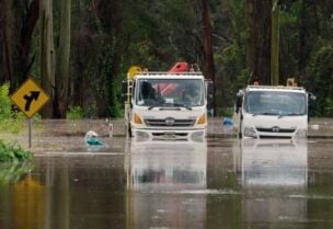 A still image taken from video shows trucks stuck in a flooded road, following heavy rains in Taree, New South Wales, Australia March 20, 2021.