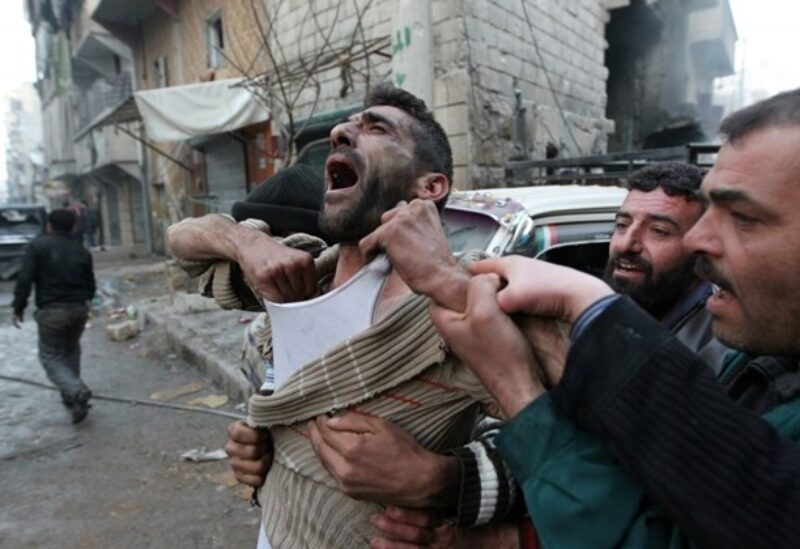 FILE PHOTO: A father reacts after the death of two of his children, whom activists said were killed by shelling by forces loyal to Syria's President Bashar al-Assad, at al-Ansari area in Aleppo, Syria, January 3, 2013.