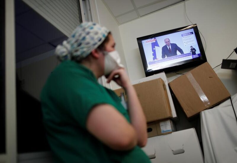 Medical staff members watch French Prime Minister Jean Castex on TV as he addresses the nation about the coronavirus disease (COVID-19) outbreak and the lockdown restrictions, at the Clinique de l'Estree - ELSAN private hospital in Stains, near Paris, France, March 18, 2021.