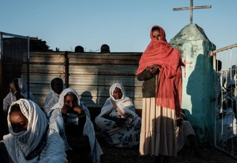 Ethiopian refugees who fled the Tigray conflict attend Sunday Mass with local believers, at an Ethiopian Orthodox church building built by former Ethiopian refugees, at the village next to Um Raquba refugee camp in Gedaref, eastern Sudan, on December 6 2020. / AFP
