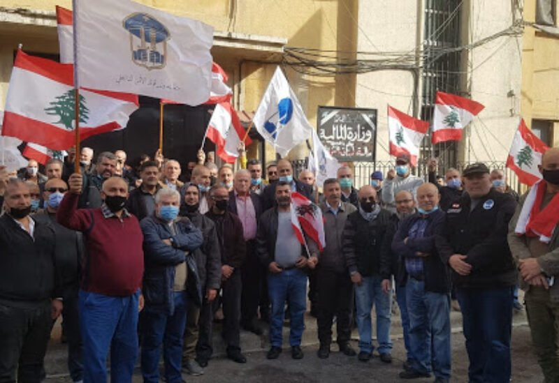 Protesters wave Lebanon, ISF flags in front of Tripoli's Ministry of Finance.