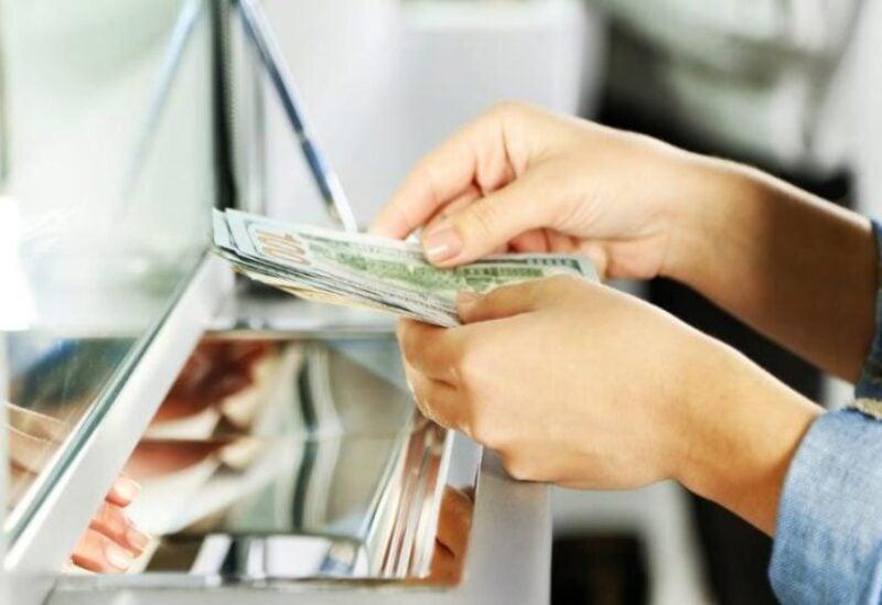 Woman counting $100 banknotes