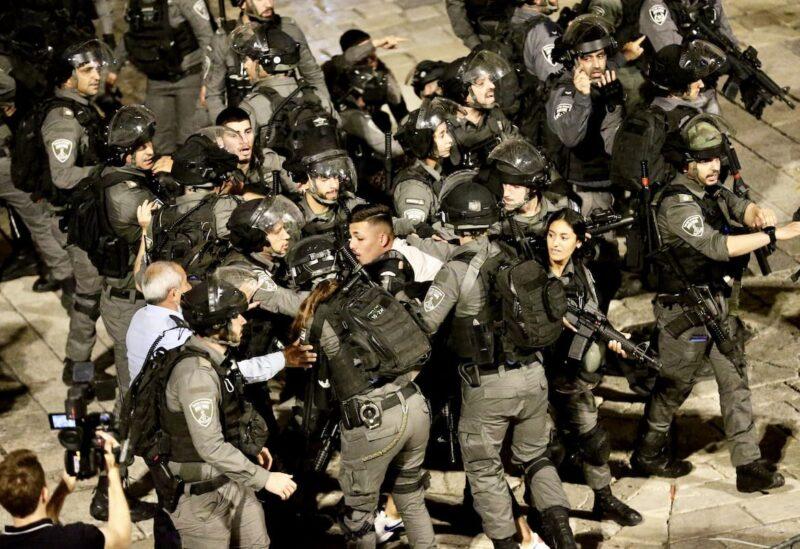 Israeli forces crowd around a Palestinian man in Jerusalem