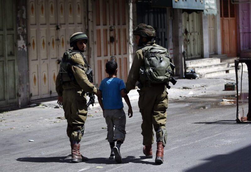 Israeli soldiers arrest a young Palestinian boy