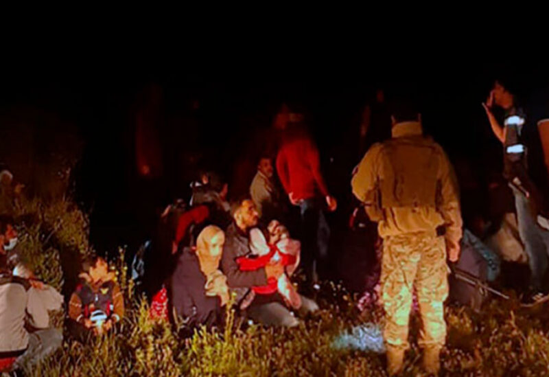 Lebanese troops stand next to Syrian migrants who tried to go by boat to the Mediterranean island of Cyprus