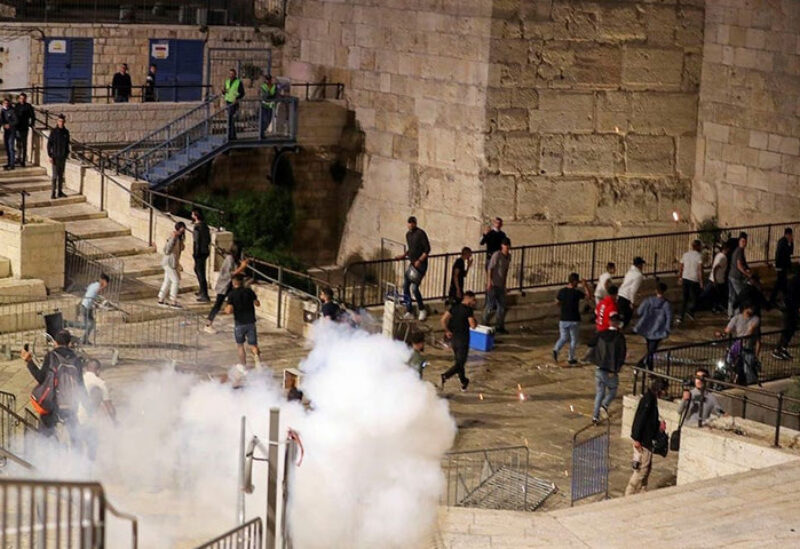 Palestinians run away as a stun grenade fired by Israeli police explodes during clashes at Damascus Gate just outside Jerusalem's Old City