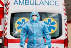 FILE PHOTO: A medical worker wearing protective gear stands next to an ambulance outside a hospital for patients infected with COVID-19 in Kyiv, Ukraine, November 24, 2020.