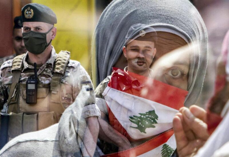 A Lebanese protester wearing a Lebanese flag face mask as members of the Lebanese Armed Forces stand guard during a demonstration against dwindling economic conditions, at Al Nour Square in the center of Tripoli, May 3, 2020. AFP