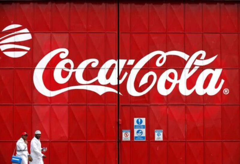 Workers walk past a Coca Cola logo painted on a gate at a Coca Cola factory in Nairobi, Kenya, June 7, 2018. REUTERS