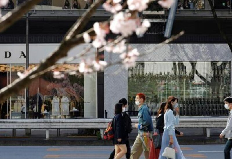 FILE PHOTO: Pedestrians wearing protective face masks amid the coronavirus disease (COVID-19) outbreak, are seen behind cherry blossoms in Tokyo, Japan, March 18, 2021.