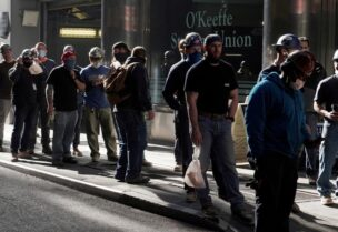 FILE PHOTO: Construction workers wait in line to do a temperature test to return to the job site after lunch, amid the coronavirus disease (COVID-19) outbreak, in the Manhattan borough of New York City, New York, U.S., November 10, 2020.