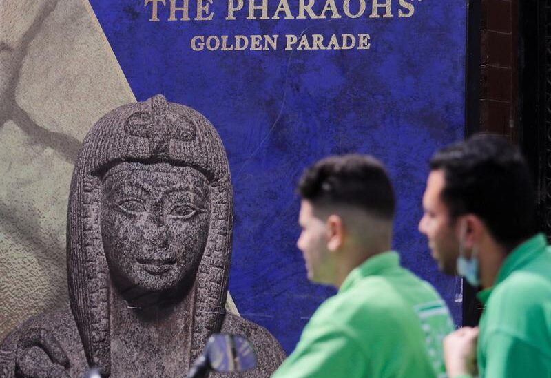 FILE PHOTO: Men pass in front of poster for pharaohs golden parade after the renovation of Tahrir Square for transferring 22 mummies from the Egyptian Museum in Tahrir to the National Museum of Egyptian Civilization in Fustat, amidst the outbreak of coronavirus disease (COVID-19), in Cairo, Egypt, April 1, 2021.