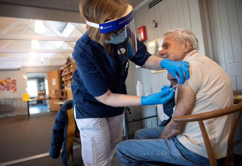 FILE PHOTO: A health worker vaccinates an elderly person with Pfizer's COVID-19 vaccine at a temporary vaccination clinic in a church in Sollentuna, north of Stockholm, Sweden March 2, 2021.
