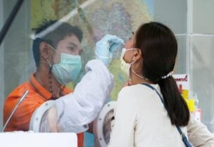 FILE PHOTO: A healthcare worker takes a nasal swab sample from a local resident for a COVID-19 test after hundreds of residents of Watthana district and the trendy Thonglor neighborhood tested positive for the coronavirus disease (COVID-19) in Bangkok, Thailand, April 8, 2021.