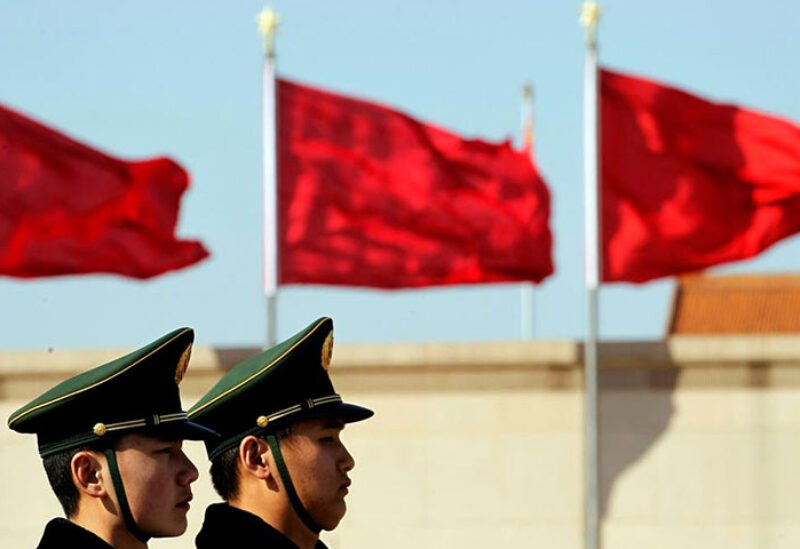 Chinese paramilitary police stand on duty near flags during the fourth plenary session of the National People's Congress held in the Great Hall of the People in Beijing, China