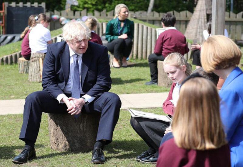 PM Boris Johnson sitting with pupils in school