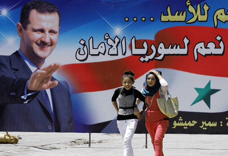People walk next to election campaign billboards depicting Syrian President Bashar al-Assad, a candidate for the upcoming presidential vote,