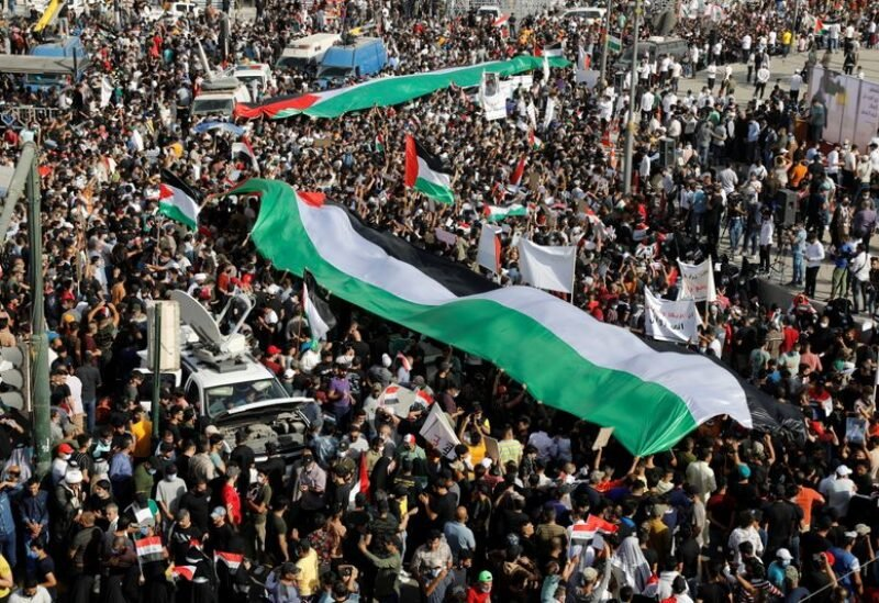 Iraqi demonstrators wave giant Palestinian flags during a protest to express solidarity with the Palestinian people amid a flare-up of Israeli-Palestinian violence, in Baghdad, Iraq May 15, 2021. REUTERS