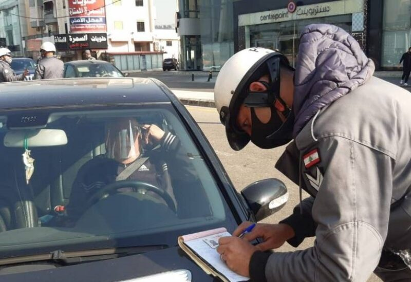 A member of Lebanon's Internal Security Forces (ISF) giving a ticket to a citizen