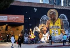 People stop by a mural of late Kobe Bryant, who perished one year ago alongside his daughter and seven others when their helicopter crashed into a hillside, in Los Angeles, California, U.S., January 26, 2021. REUTERS