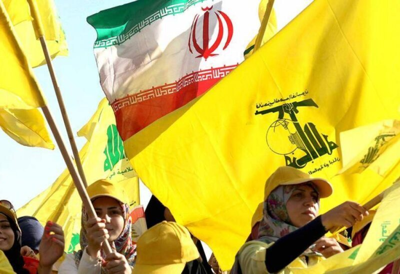 Members of Hezbollah raising both the patry's and the Iranian flags.