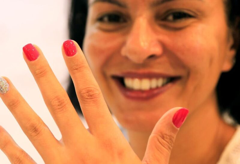 A customer looks on as she gets a microchip, containing personal data, attached to one of her nails at Lanour Beauty Lounge in Dubai. (File photo: Reuters)