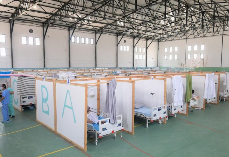 Tunisian doctors are stand next to rows of patients at a gym that was converted to deal with a surge in new COVID-19 infections in the east-central city of Kairouan on July 4, 2021. (File photo)