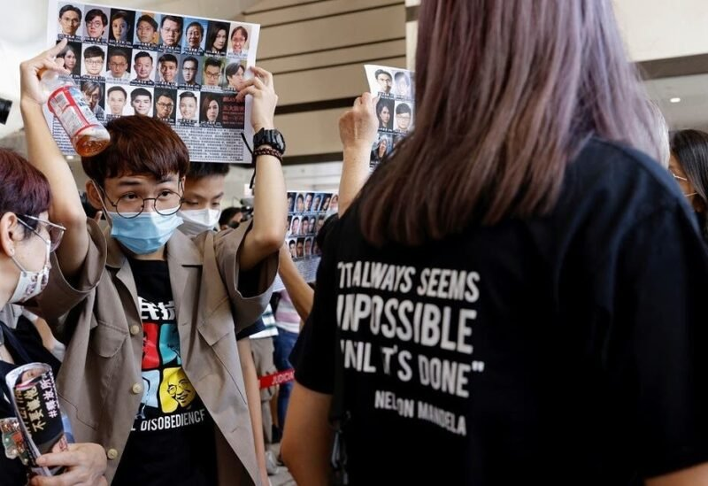 Supporters hold up placards among people queuing up at the West Kowloon Magistrates' Courts for a hearing of 47 pro-democracy activists charged with violating the national security law, in Hong Kong, on July 8, 2021. (Reuters)
