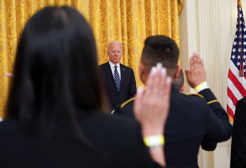 U.S. President Joe Biden watches as hands are raised for the Oath of Allegiance during a naturalization ceremony at the White House in Washington, U.S., July 2, 2021. REUTERS/Kevin Lamarque