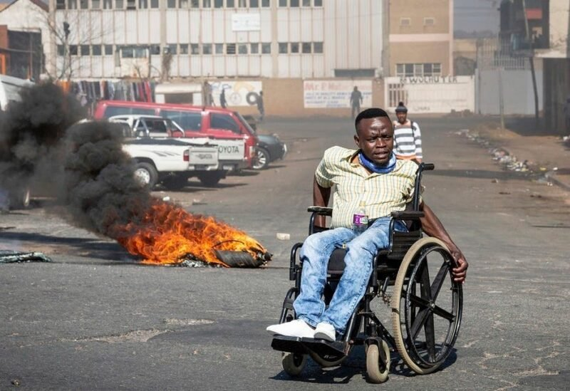 A protester in a wheelchair passes a burning tyre in Johannesburg, Sunday, July 11, 2021. (AP)