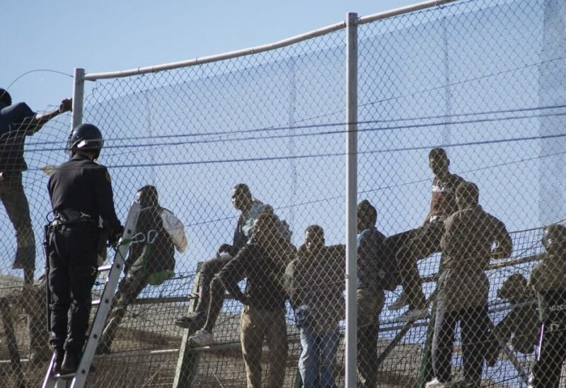 African migrants sit on top of a border fence during an attempt to cross into Spanish territories, between Morocco and Spain's north African enclave of Melilla, November 21, 2015. (File photo: Reuters)