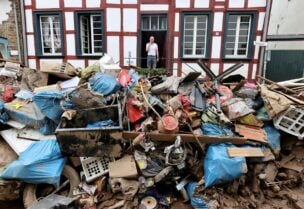 A man looks on outside a house in an area affected by floods caused by heavy rainfalls in Bad Muenstereifel, Germany, July 19, 2021. REUTERS/Wolfgang Rattay/File Photo