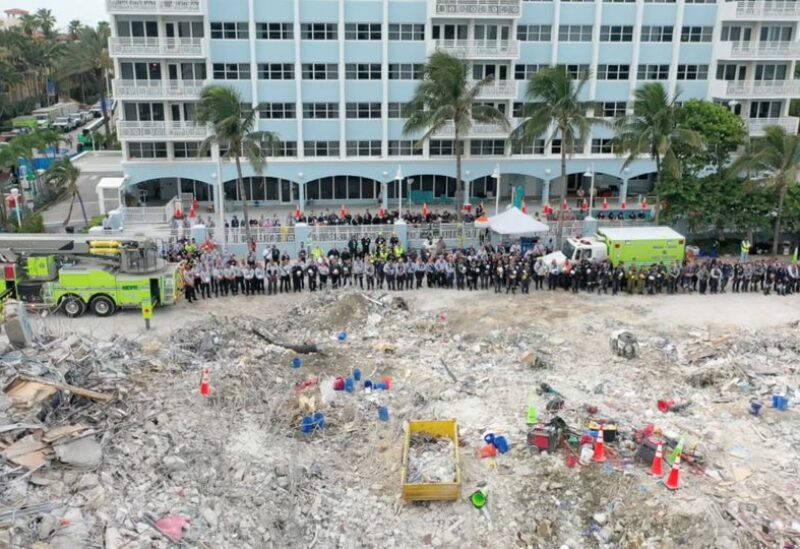 Members of the search and rescue team stand during a moment of silence in front of the rubble of the collapsed Champlain Towers South building in Surfside, Florida, U.S. July 7, 2021, in this still image taken from drone footage obtained from social media. Mandatory credit MIAMI-DADE FIRE RESCUE/via REUTERS